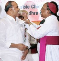 YSR taking communion from a Christian priest.