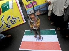 Pakistan Muslim boy standing on Indian flag.