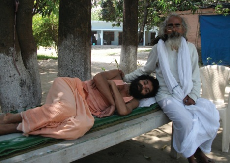 Swami Nigamananda rests in the lap of his guru Swami Shivananda .
