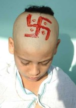 Hindu boy with a swastika drawn on his head during a upanayana ceremony.