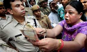 Delhi anti-rape protester offering money to the police (as the police had offered money to the rape victim's parents to be quiet).