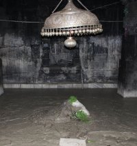 Kedarnath linga in silt with bilva leaves.