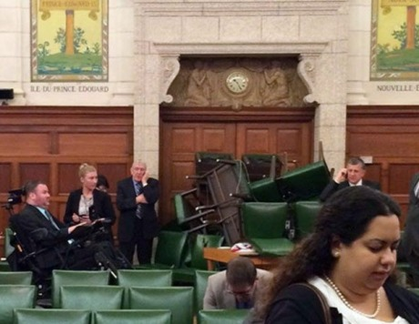 In this photo provided by Conservative MP Nina Grewal, members of Parliament barricade themselves in a meeting room on Parliament Hill in Ottawa, Canada, Wednesday, Oct. 22, 2014, after shots were fired in the building. A gunman with a scarf over his face shot to death a Canadian soldier standing guard at the nation's war memorial Wednesday, then stormed Parliament in a hail of gunfire before he was killed by the usually ceremonial sergeant-at-arms, authorities and witnesses said. (AP Photo/The Canadian Press, Nina Grewal)