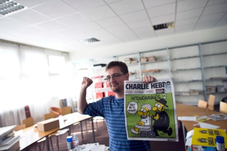 "French satirical weekly Charlie Hebdo's publisher and cartoonist, known only as Charb, clenches his fist as he presents to journalists, on September 19, 2012 in Paris, at the headquarters, the last issue which features on the front cover a satirical drawing entitled ""Intouchables 2"". Inside pages contain several cartoons caricaturing the Prophet Mohammed. The magazine's decision to publish the cartoons came against a background of unrest across the Islamic world over a crude US-made film that mocks Mohammed and portrays Muslims as gratuitously violent. The title refers to ""Intouchables"", a 2012 French movie, the most seen French movie abroad, which is selected to represent France for the Oscars nominees, according to one of his directors, Eric Toledano. AFP PHOTO FRED DUFOUR"