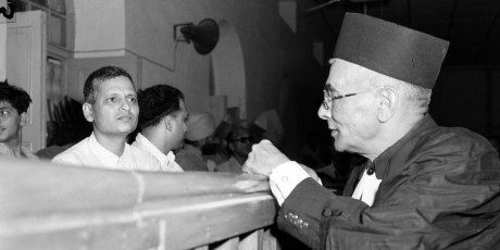 Nathuram Godse, left, one of nine co-defendants in the Mohandas Gandhi assassination conspiracy case, and defense counsellor L. B. Bhopatkar confer May 27, 1948, at the start of the hearing.  (AP Photo)