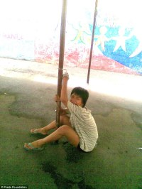 Manila street girl chained to pole.
