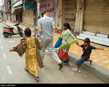 A western tourist gives money to child beggars in India