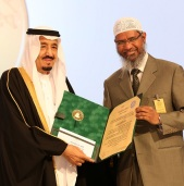 """A handout picture released by the King Faisal Foundation on March 1, 2015 shows Saudi King Salman bin Abdul Aziz (L) presenting Zakir Naik, president of the Islamic Research Foundation in India, with the 2015 King Faisal International Prize for Service to Islam in Riyadh. Naik was honoured for being one of the most renowned non-Arabic speaking promoters of Islam. He founded the Peace TV channel, billed as the world's only channel specialising in comparative religion. AFP PHOTO / HO / King Faisal Foundation == RESTRICTED TO EDITORIAL USE - (MANDATORY CREDIT """"AFP PHOTO / HO / King Faisal Foundation"""" )"""