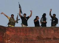 Indian security personnel celebrate on the roof of a police station after a gunfight in Dinanagar town, in Gurdaspur district of Punjab, India, July 27, 2015.