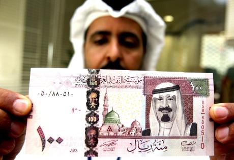 Saudi banker displays the new one hundred riyal note