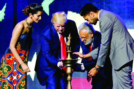Republican Hindu Coalition Chairman Shalli Kumar (2nd R) helps Republican presidential nominee Donald Trump (2nd L) light a ceremonial diya lamp before he speaks at a Bollywood-themed charity concert put on by the Republican Hindu Coalition in Edison, New Jersey, U.S. October 15, 2016. REUTERS/Jonathan Ernst