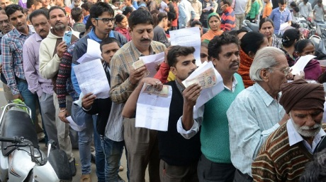People queue outside a bank as they wait to deposit and exchange 500 and 1000 rupee notes in Amritsar on November 13, 2016. India's cash machines will take several weeks to reset with new bills,