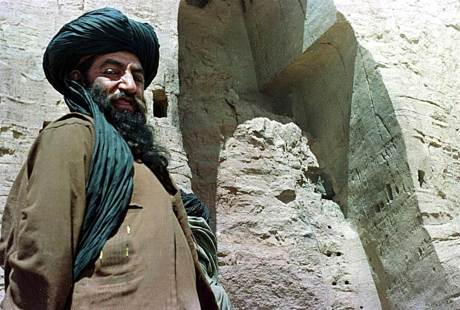 An unidentified official of the Afghan Taliban stands near a destroyed Buddha statue in Bamiyan, Afghanistan, on March 26, 2001.