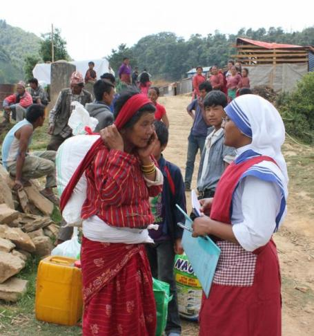 Sister Marica, a member of the Missionaries of Charity, chats with an elderly woman carrying earthquake relief material in the mountains overlooking Kathmandu Valley