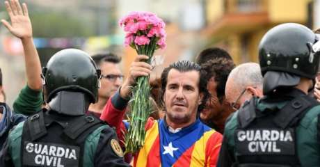 A man dressed in the Catalonian flag holds up pink flowers as police move in on the crowds of voters gathered on October 1, 2017 in Sant Julia de Ramis, Catalonia.