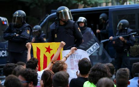 A protestor holds up an Estelada (Catalan flag) in front of a line of Spanish police.