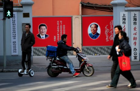 People cross a street in front of posters depicting late Chairman Mao Zedong (R) and China's President Xi Jinping in Shanghai.