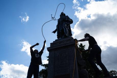 Mike Forcia, who is Anishanaabe, left, and another man fasten ropes around the neck of a statue of Christopher Columbus at the Minnesota State Capitol in St. Paul on June 10, 2020.