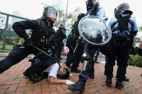 Hong Kong police restrain a protester.
