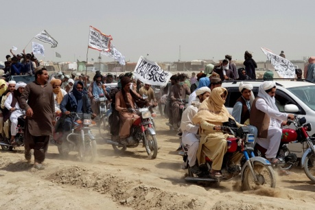 People on vehicles, holding Taliban flags, gather near the Friendship Gate crossing point in the Pakistan-Afghanistan border town of Chaman, Pakistan on July 14, 2021.